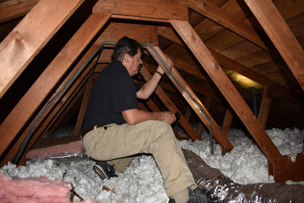 John Myers carefully inspecting an attic